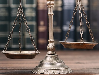 Scales resting on a wooden table with legal books in the background